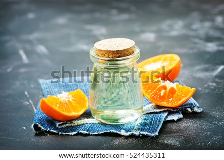 orange oil in a glass bottle with fresh oranges