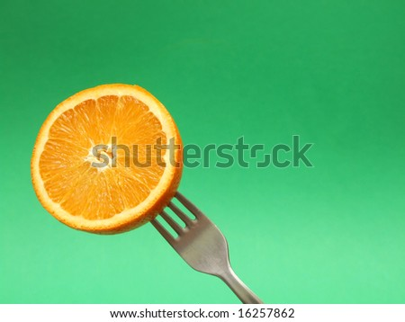 orange on fork with green background