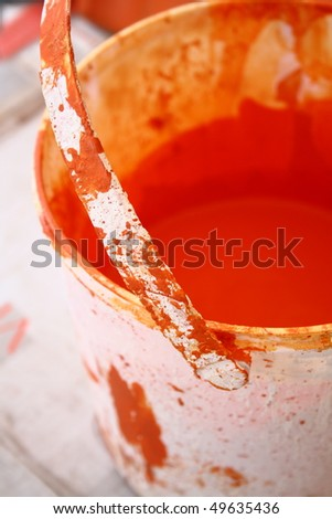 Orange paint in an old used bucket - stock photo