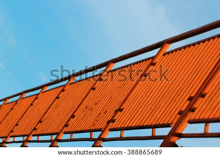 Orange painted metal fence against blue sky background, perspective view. Focus is in the middle