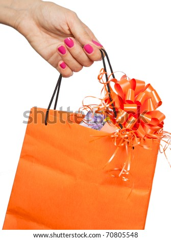 Orange paper bag with a gift in a women hand - stock photo