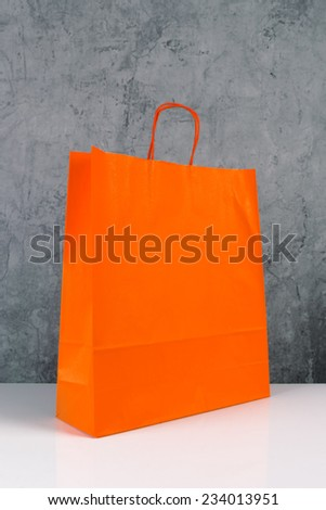 Orange Paper Shopping Bag on Wooden Retail Store Table. - stock photo