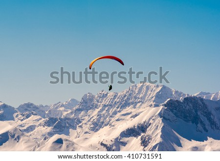 orange paraglider flying through the austrian alps  - stock photo