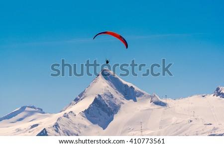 orange paraglider in front of kitzsteinhorn, austrian alps - stock photo