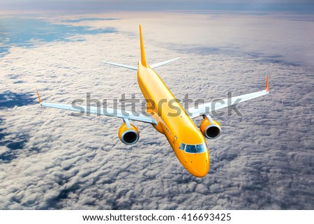 Orange passenger jet plane is flying high above the clouds - stock photo