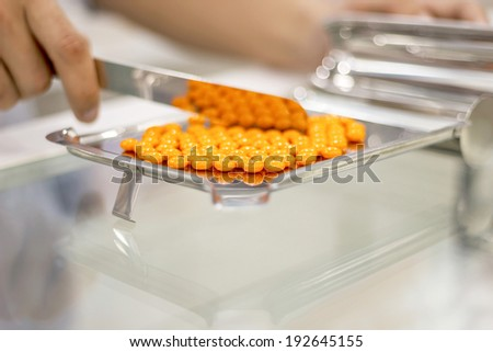 Orange pill on a counting tray - stock photo