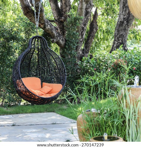 Orange pillow on modern swing in the garden. - stock photo