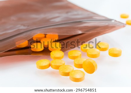 Orange pills for inflection and swelling cure with brown slider plastic bag to protect the pills away from light. Orange pills with slider plastic on with background. - stock photo
