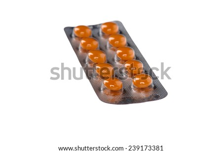 Orange pills in blisters on white background - stock photo