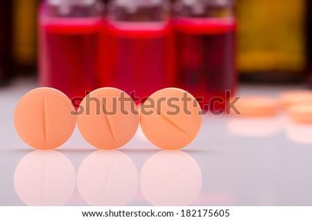 Orange pills on white surface against small vaccine bottles  - stock photo