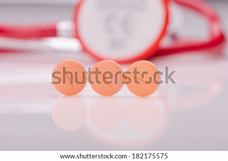 Orange pills on white surface and a stethoscope    - stock photo