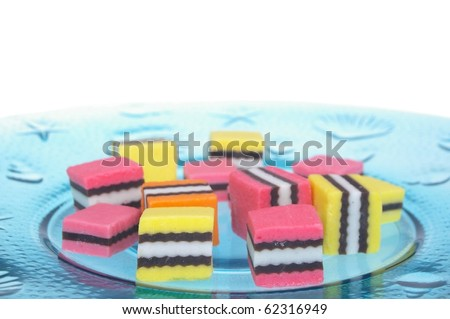 orange pink and yellow licorice on plate - stock photo