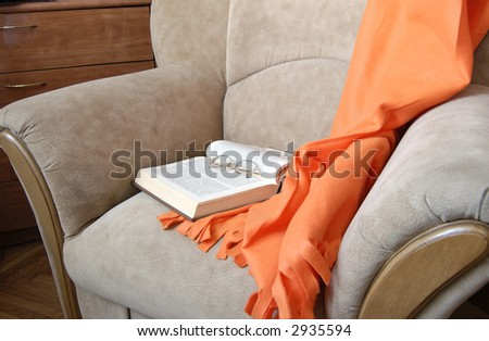 orange plaid, open book, glasses leaved in beige chair
