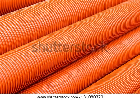Orange plastic PVC pipes - abstract industrial object concept - stock photo