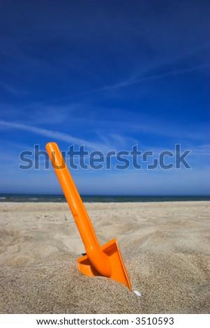 Orange plastic spade in the sandy seashore - stock photo