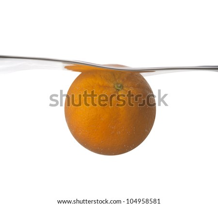 Orange plunging into cold water - stock photo