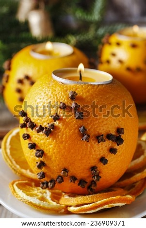 Orange pomander ball with candle. Christmas decorations in the background - stock photo