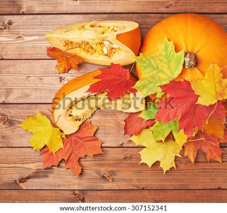 Orange pumpkin and maple leaves composition over the background made of brown wooden boards - stock photo
