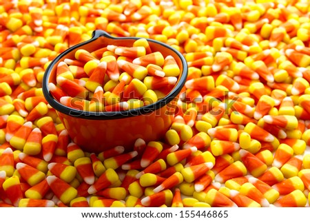 Orange pumpkin bowl filled with candy corn candy - stock photo