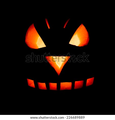 Orange pumpkin face carved for Halloween isolated on black - stock photo