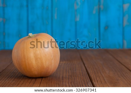 Orange pumpkin on blue wooden background, with empty space for text. Autumn scene. - stock photo