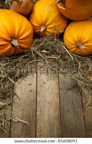 orange pumpkins lay on a wooden background with a straw - stock photo