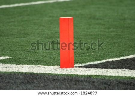 Orange pylon on the goal line on the football field with artificial turf. - stock photo