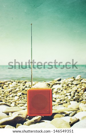 Orange radio set on the beach as old photography. - stock photo