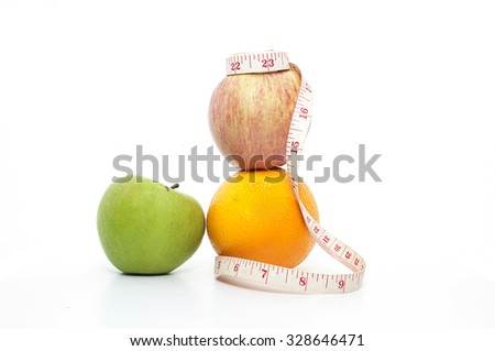 Orange, red and green aples with yellow measuring tape - stock photo