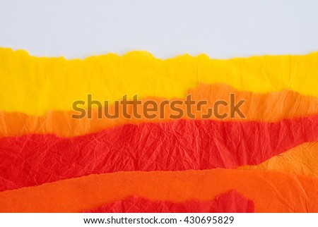 orange, red and yellow wrinkled torn paper - material sample - close up of textured background - stock photo