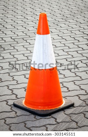 Orange, reflective white and black temporary movable traffic cone on grey paved street with lines of tires - stock photo