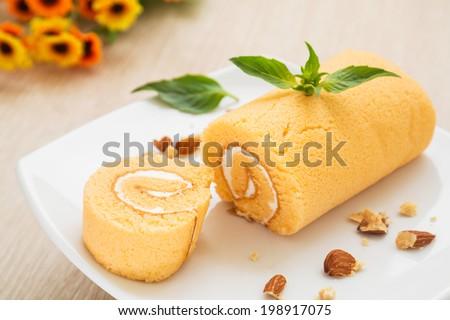 Orange roll cake on plate - stock photo