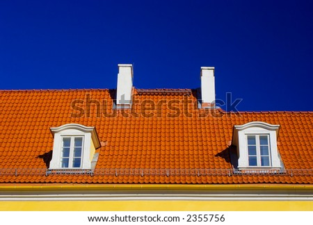 Orange roof with two windows and chimneys against blue sky - stock photo