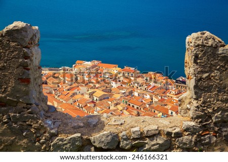 orange roofs of Cefalu old houses through the bastion's wall, Sicily - stock photo