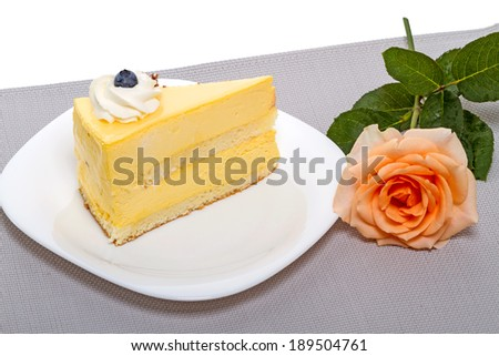 Orange rose and a piece of cake with blueberries - stock photo