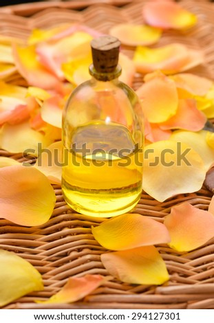 Orange rose and petals with massage oil on bamboo mat  - stock photo