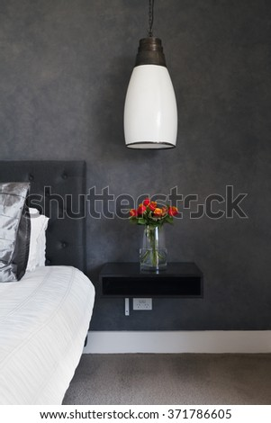 Orange roses on bedside table in contemporary dark bedroom design with pendant lighting - stock photo