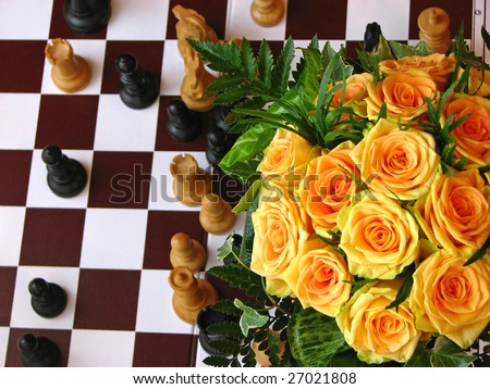 Orange roses with chess figures - stock photo