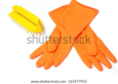 Orange rubber glove and clean brush on white background