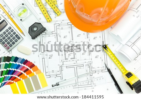 Orange safety helmet with project blueprints and construction tools - stock photo