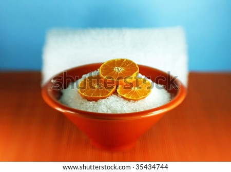 Orange-scented aromatherapy bath salts with slices of tangerine and a spa towel