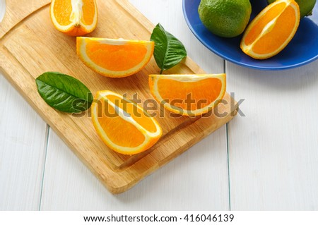Orange segments with leaves on cutting board and white wooden surface - stock photo