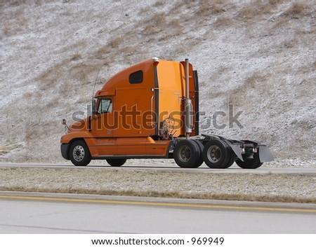 Orange Semi Truck on Highway - stock photo