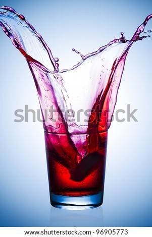 Orange slice making a large soda splash in a glass. - stock photo