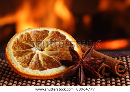 orange slice with anis and cinamon sticks on bamboo mat in front of fireplace - stock photo
