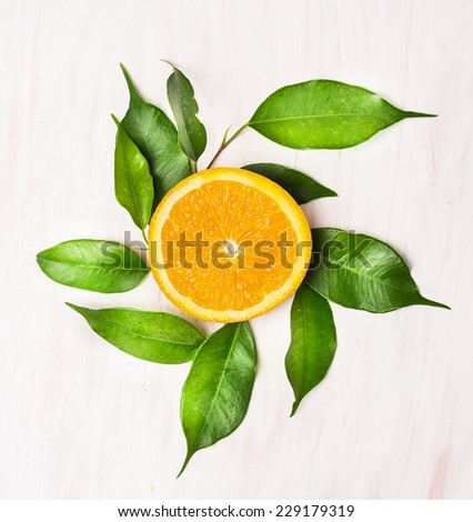 orange slice with green leaves on white wooden table , top view - stock photo