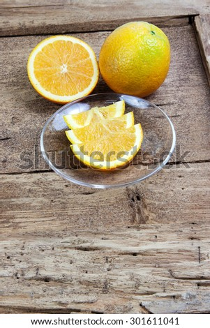 Orange sliced in half and thinly sliced on old table wood - stock photo