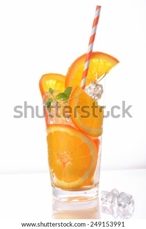 orange slices and ice cubes in cup with tube on white background  - stock photo
