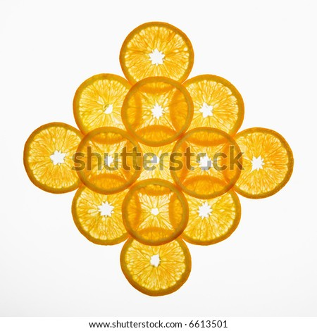 Orange slices arranged in design on white background. - stock photo