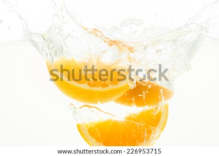 Orange Slices falling deeply under water with a big splash - stock photo